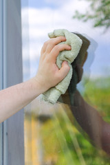 Male hand with rag washing window outdoors