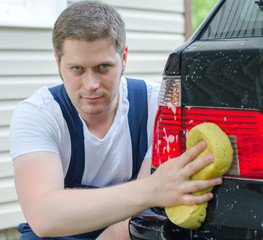 Young worker washing car with yellow sponge