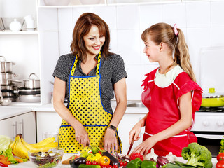 Mother and daughter cooking at kitchen.