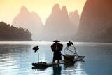 YANGSHUO - JUNE 18: Chinese man fishing with cormorants birds in