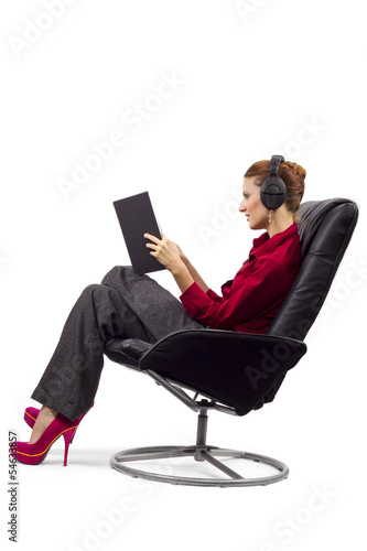 Woman listening to audio book and holding a textbook