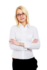 A young woman wearing glasses standing