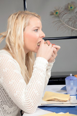 Hungry woman eating a roll