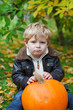 Little toddler with big orange pumpkin in garden