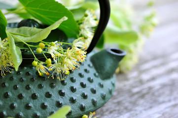 Teapot with linden tea and flowers, close-up