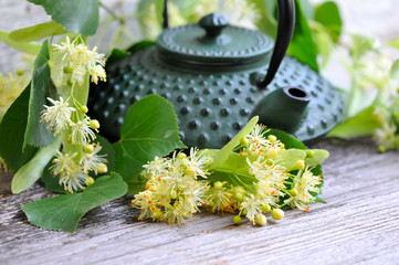 Teapot with linden tea and flowers on old wooden background