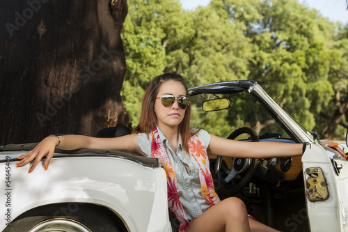 Foto op Canvas Snelle auto s View of a beautiful woman posing on a white convertible car.