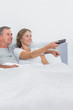 Relaxed couple watching tv in bed