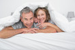 Cheerful couple under the duvet