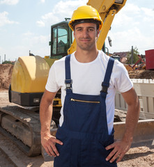 Friendly construction worker in front of his excavator