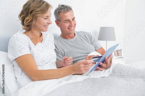 Cheerful couple using their tablet pc to buy online