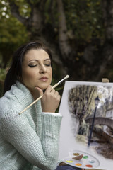 young woman painting on a park