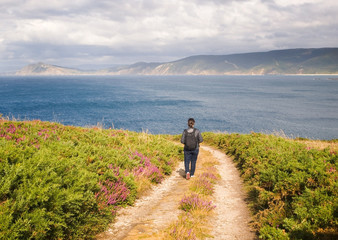 Woman walking along a path on the coast