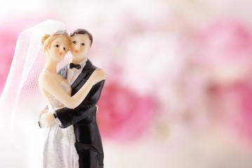 Figurines of wedding cake topper with flowers in background