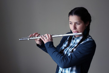 Teenage girl plays the flute.