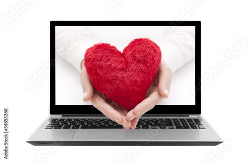Laptop with red heart in woman hands. Clipping path included.