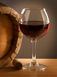 Red wine glass and barrel on a wooden table