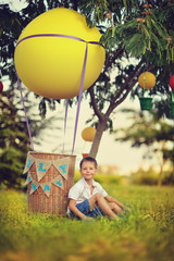 on the green grass boy sits near the balloon with a basket
