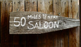 Wild West Rustic Wooden Sign Pointing To Next Saloon