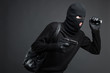 Thief. Side view of men in black balaclava holding a gun and fla