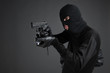 Criminal. Side view of men in black balaclava aiming with a gun