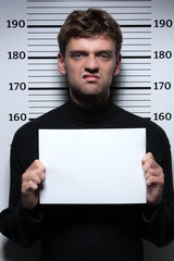 Busted burglar. Angry burglar holding a white poster while stand