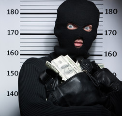 Busted burglar. Angry burglar holding a bag with stolen goods wh