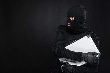 Stealing a suitcase. Frustrated thief in black balaclava holding