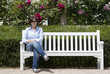A woman sitting at a garden bench