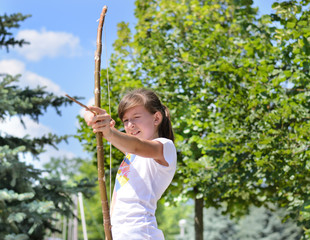 Young girl practising with a bow and arrow