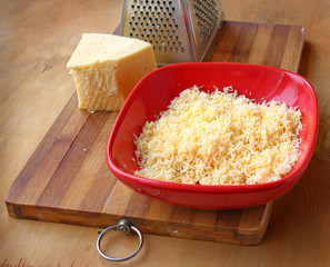 Rubbed cheese in a red bowl