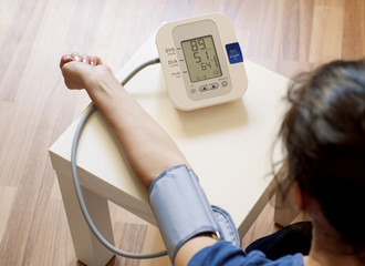 Young woman measuring her blood pressure