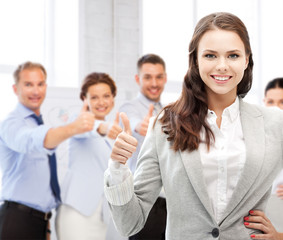 businesswoman showing thumbs up in office