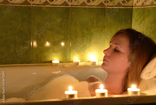 The girl takes a bathtub at candles
