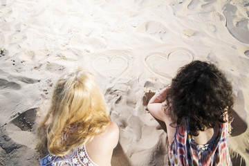 Two young womans draw hearts on sand.