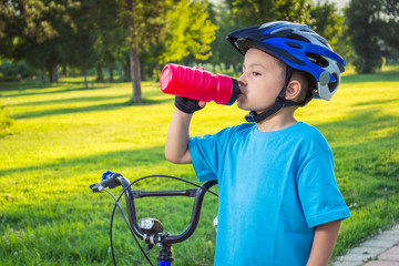 Little boy drinking water by the bike