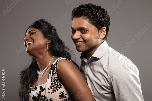 Fashionable passionate indian couple. Studio shot against grey.