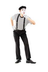 Full length portrait of a male mime artist gesturing silence