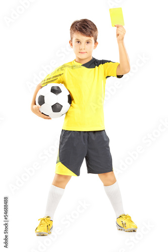 Kid in sportswear holding soccer ball and giving yellow card