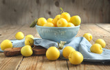 Yellow plums in blue bowl. Selective focus