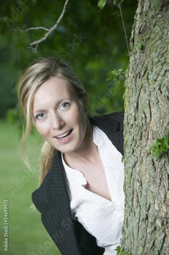 Junge lachende blonde Frau hinter einem Baum
