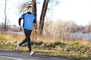 Male runner man running in autumn on cold day