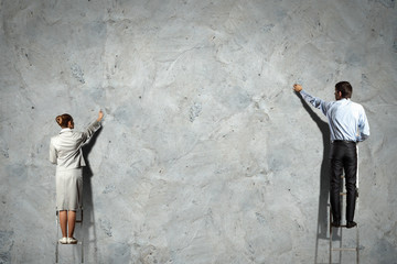 businesspeople drawing diagrams on wall