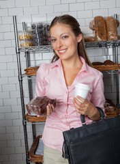 Woman Holding Cake And Coffee Cup At Store