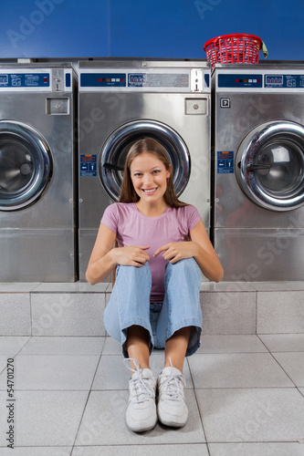 Woman Sitting Against Washing Machines At Laundry
