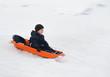 boy rides a sled winter