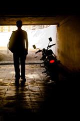 Man in dark tunnel near motorbike