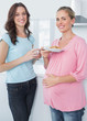Smiling pregnant woman and her friend