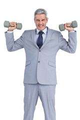 Strong businessman lifting dumbbells