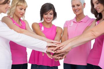 Cheerful women posing in circle holding hands wearing pink for b